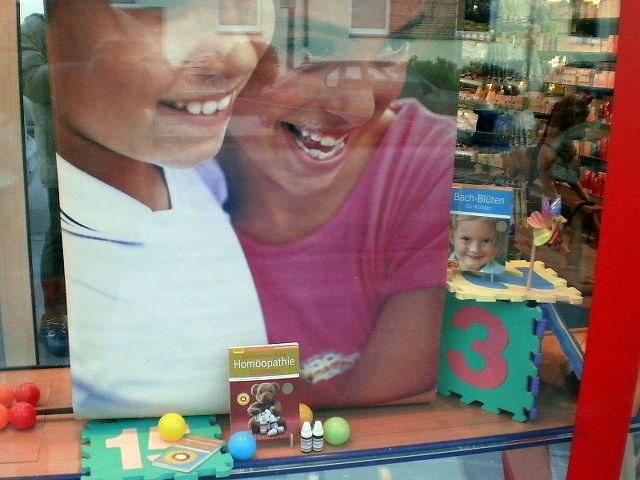 Werbung im Schaufenster einer Apotheke: Homöopathie für Kinder, Bachblüten für Kinder -- mit Bildern von glücklichen Kindern, verstehts sich