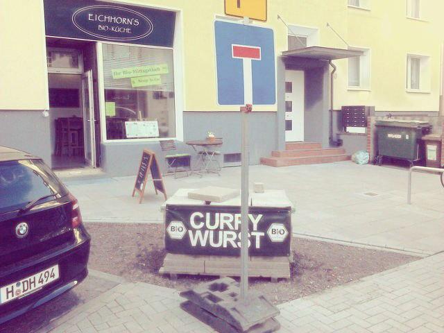Eine Werbung für 'Bio'-Currywurst vor einem 'Bio'-Restaurant, davor steht ein provisorisches Verkehrsschild 'Sackgasse'