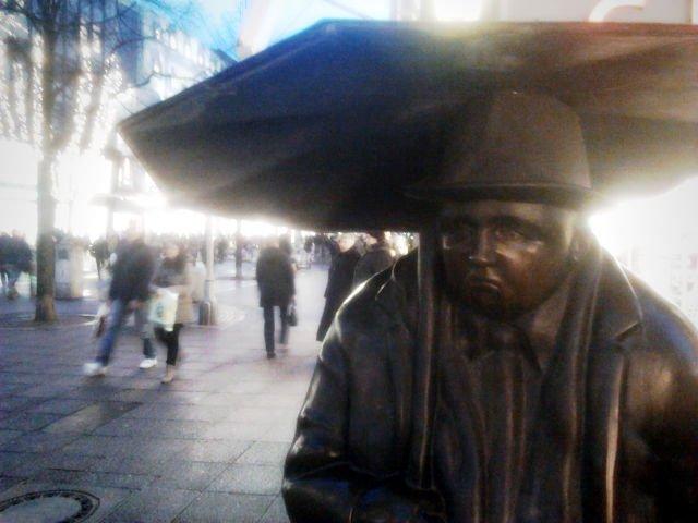 Kunstwerk am Kröpcke (Stadtzentrum Hannovers): Ein offensichtlich griesgrämiger Fußgänger mit Regenschirm. Dazu Kunstlicht und Osramkerzen der Weihnachtszeit, Regenwetter und ein Abend.