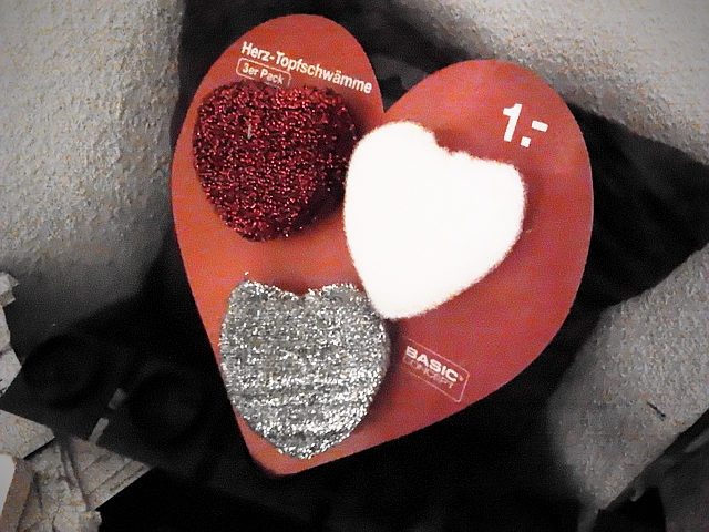 Drei auf einem herzförmigen Stück Pappe angebrachte Topfschwämme, ebenfalls in Herzform. Auf der Pappe der Text: 'Herz-Topfschwämme, 3er Pack, 1,-; BASIC CONCEPT