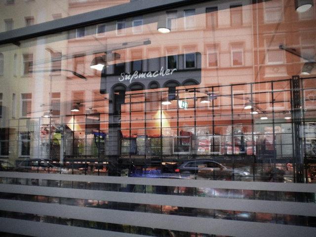 Schaufenster eines großen, so genannten 'Bio-Marktes' in Hannover. Durch das Fenster wird ein Hinweisschild 'Süßmacher' sichtbar. Im Fenster spiegelt sich die Stadt mit ihren Häusern und mit dem Autoverkehr.